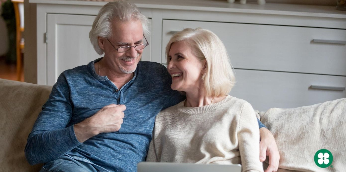 Retired couple laughing on a couch