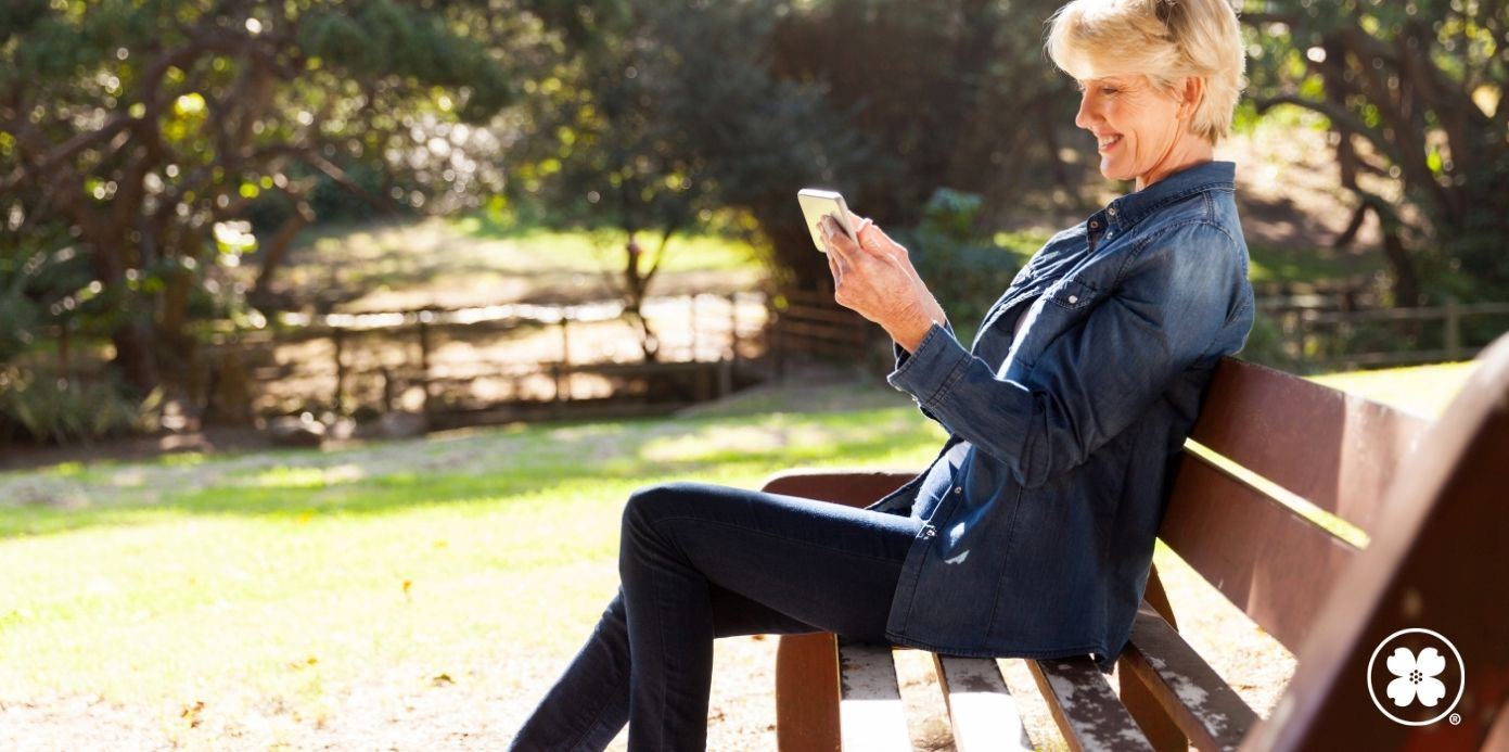 Lady sitting on a bench looking at her phone